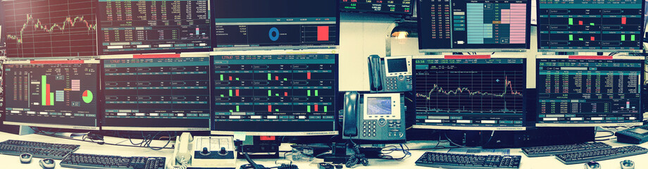 Display of Stock market quotes and chart in monitor computer room with business office equipments .business and money concept, panorama with grainy style
