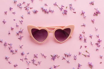stylish pink hearted boho sunglasses on pink background with lilac flowers. creative trendy flat lay with space for text. modern fashion and girly image. summer vacation concept