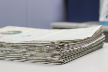 Closeup - Newspaper Stack on white table in office