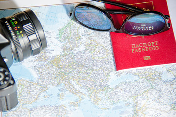 Adventure concept. Sunglasses, retro black camera and passport on map