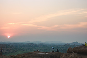 Picturesque view from the Malyavanta Hill at sunset overcast sky in Hampi, Karnataka, India. Tourists enjoy and photograph the sunset