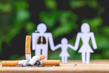 Paper dolls, parents and daughter. Daddy doll have burned lungs. Their hands hold hands with their daughter. There are burned cigarettes butts.