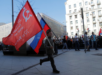 A boy carries a Russian flag and a replica of the so-called Victory Standard as he takes part in the Immortal Regiment march during the Victory Day celebrations in central Moscow