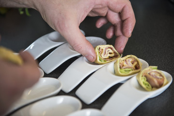 Cook preparing pancake wraps as appetizers on porcelain spoons