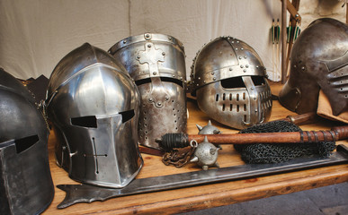 Shiny metal helmets of medieval knights with traditional weapons at a middle age theme festival
