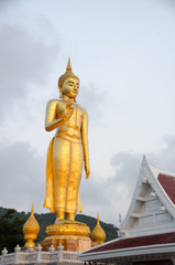 Standing Buddha image.The attitude of persuading the relatives not to quarrel symbol of Golden Buddha statue  at Kho Hong Hill, Hatyai, songkhla, Thailand