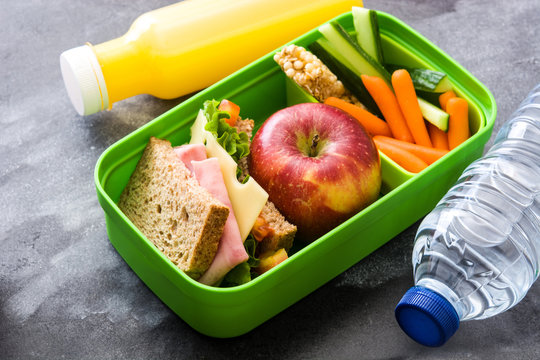 Healthy school lunch box: Sandwich, vegetables ,fruit and juice on black stone