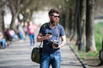 Young male photographer stroll around city in search for perfect picture. Bearded man in stylish eyewear holding vintage film camera and top-notch smartphone, modern gadgets vs old-fashioned devices