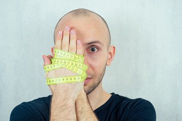 portrait of a young bald man with hands tied with a measuring tape. concept of diet and anorexia