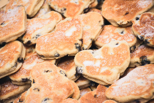 Traditional Welsh cakes with raisins and powdered sugar macro in heart shapes