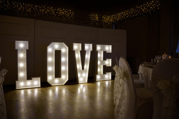 Illuminated Love sign in large letters at a wedding reception