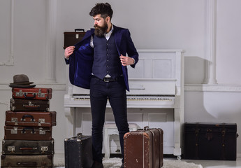 Hotel service concept. Man, traveller with beard and mustache with luggage, luxury white interior background. Macho elegant on strict face stands near pile of vintage suitcase, arrived to hotel.