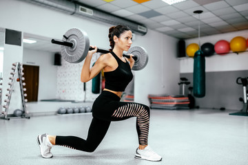 Athletic woman doing weighted lunges with barbell on a back.