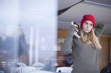 Bellissima ragazza, vestita con un maglione verde e una cuffia rossa tiene in mano un libro e guarda fuori dalla finestra.