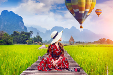 Wall Mural - Young woman sitting on wooden path and look at balloons with green rice field in Vang Vieng, Laos.