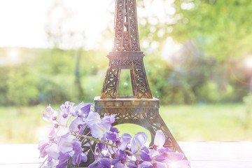 Eiffel tower in the green park with purple wisteria
