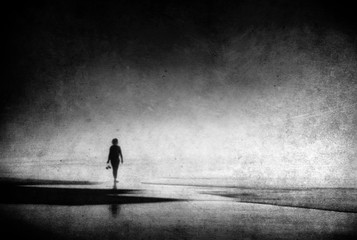 lonely woman walking on beach with grungy textures