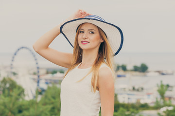 Attractive woman wearing sun hat and white top