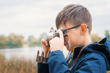 Boy child outdoors holding an old camera.