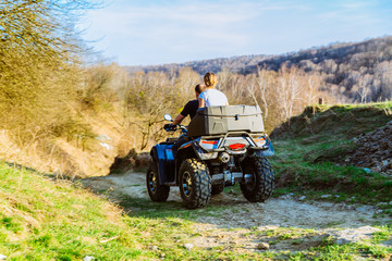 couple enjoys riding an ATV on forest hills