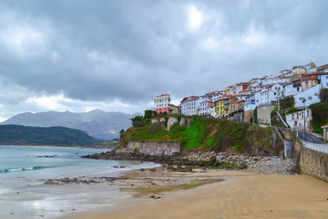 View from the beach of Lastres, Asturias, Spain, of the town, in a cloudy day. Small town in front of the sea over a cliff.