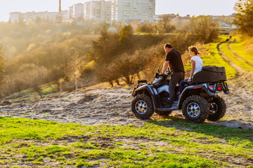 couple enjoys riding an ATV on forest hills on sunset