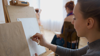 Young female painter draws sketches in drawing studio