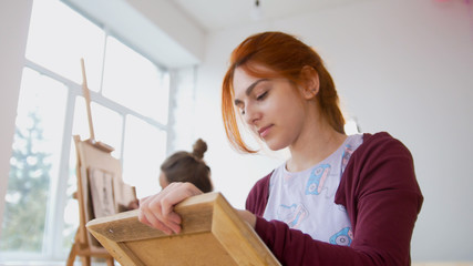 Young female woman in front of artist draws sketches of woman figure
