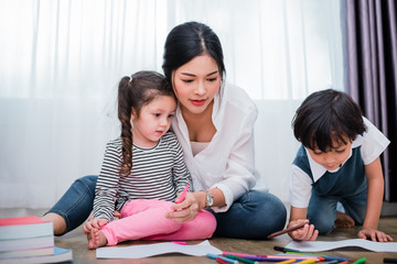 Mother teaching children in drawing class. Daughter and son painting with colorful crayon color in home. Teacher training students in art classroom. Education and Learning development of kids theme.
