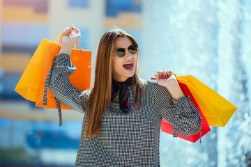 Beautiful girl in sun glasses is holding shopping bags and smiling while walking down the street