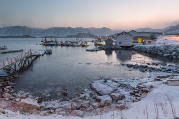 Fishing harbor in fiord at sunset in winter, Norway
