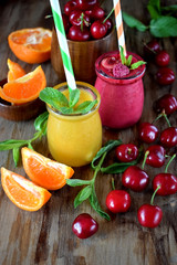 Yellow and red smoothies in glass jars surrounded by mandarins and cherries