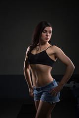 Portrait of attractive woman with muscular body. standing on dark background. Fit and sexy young female bodybuilder posing.