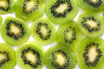 Many slices of ripe and juicy KIWI on a white surface