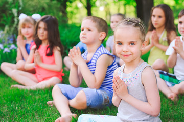 A large group of children engaged in yoga in the Park sitting on the grass.