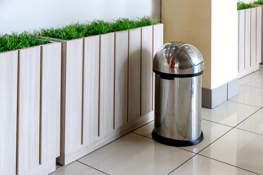 stainless steel trash can stands near the fence with greenery