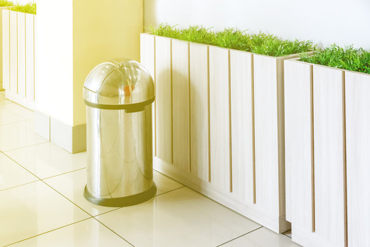 stainless steel trash can stands near the fence with greenery, tone