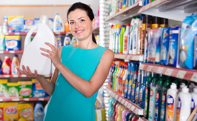 Smiling female want to buying softener in bottle