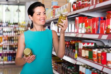 Girl is holding jar of preserved olives