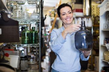 Portrait of positive woman choosing fragile glass item