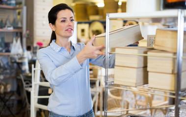 Positive woman choosing design box in decor store
