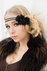 Closeup portrait of blond actress playing in 1920s movie. Pretty girl in headband and fur collar isolated in white background
