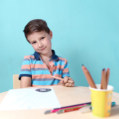 Cheerful smiling Caucasian boy spending time drawing with colorful pencils at home. He is looking into the camera.