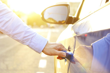 Young man, businessman in formal wear opens door of new car, caribbean blue color, close up of hand on handle, reflection on polished vehicle body surface. Soft sunset light. Background, copy space.