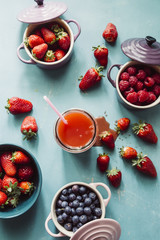 Summer fruit background, top view of berries inside ceramic colored cocotte, blueberries, strawberries, raspberries, flat lay, blue table, wth a glass full of juice and spilling.