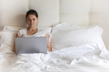 Portrait pretty young girl with laptop on bed in modern apartment in the morning