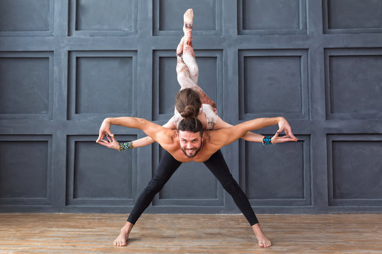 Yoga class couple and group concept. Young couple meditating together, doing exercise on urban background