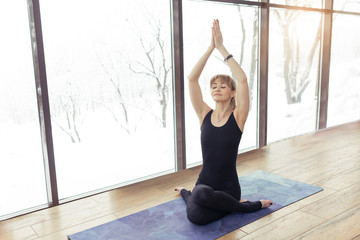 Young woman yoga practitioner or pilates trainer exercising indoors in various poses or asanas on blue mat