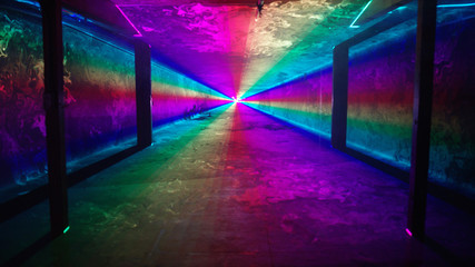 Rainbow laser light tunnel shines past columns at nightclub, background 3