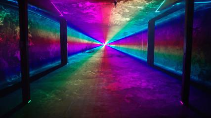 Rainbow laser light tunnel shines past columns at nightclub, background 3